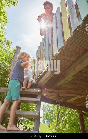 Niedrigen Sie Vater und zwei Söhne, Malerei Baumhaus, Winkel Ansicht - Stockfoto
