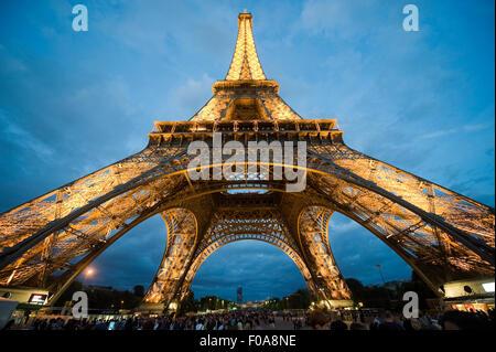 Touristen besuchen den Eiffelturm in der Dämmerung in Paris in Frankreich - Stockfoto