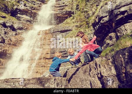 Gruppe von Kindern Kletterfelsen neben Wasserfall - Stockfoto