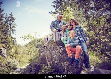 Porträt der Familie sitzen auf Felsen im Wald - Stockfoto
