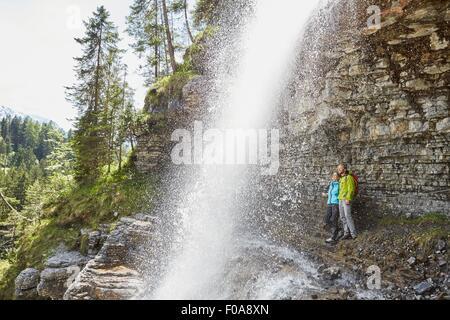 Junges Paar stehen unter Wasserfall, auf der Suche, Tirol, Österreich - Stockfoto