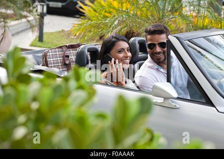 Mitte erwachsenes paar im Cabrio, Frau mit smartphone - Stockfoto