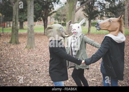 Drei Schwestern tragen Masken tanzen im park - Stockfoto