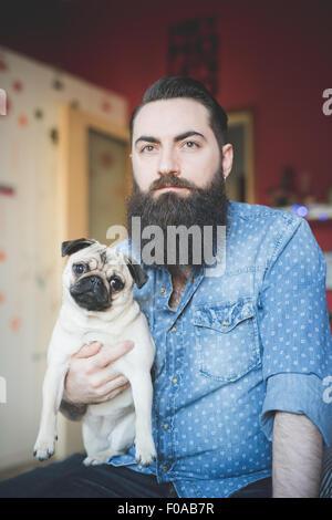 Young bärtiger Mann mit Hund auf Arm - Stockfoto