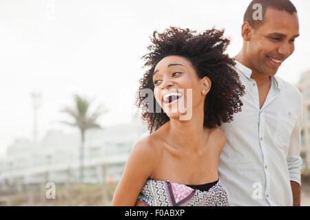 Junge Frau lachend mit Freund beim Spaziergang am Strand, Rio De Janeiro, Brasilien - Stockfoto