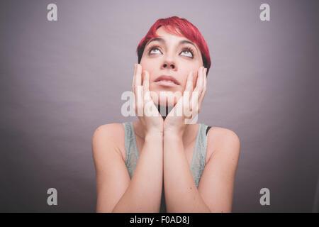 Studio-Porträt der jungen Frau mit kurzen rosa Haaren mit Händen auf Wangen - Stockfoto