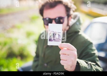 Porträt von Mitte erwachsener Mann hält eine sofortige Aufnahme von sich selbst - Stockfoto