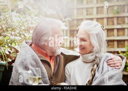 Älteres paar verpackt in Decke im Garten - Stockfoto