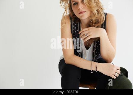 Mitte Erwachsene Frau ruhenden Ellenbogen am Knie sitzen - Stockfoto