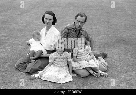 Ein Familienporträt, Mutter, Vater, zwei Töchter und ein Baby, alle sitzen auf dem Rasen im Garten. - Stockfoto
