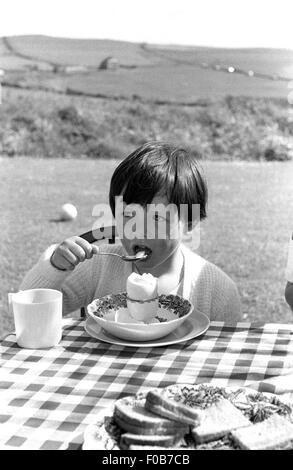 Ein junges Mädchen am Tisch essen ein gekochtes Ei im Garten - Stockfoto