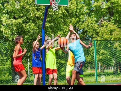 Gruppe von glücklichen Jugendlichen Basketball spielen - Stockfoto