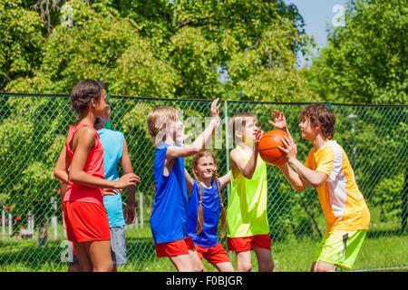 Glückliche Freunde spielen Basketballspiel außerhalb - Stockfoto
