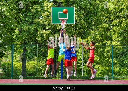 Glückliche Jugendliche spielen Basketball auf Spielplatz - Stockfoto