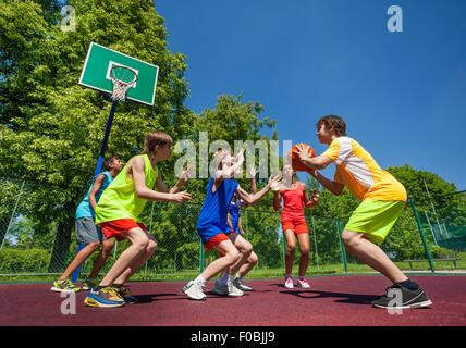Kinder im Teenageralter Basketball-Spiel zusammen spielen - Stockfoto