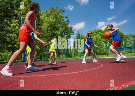 Teenager-Team Basketball-Spiel zusammen spielen - Stockfoto