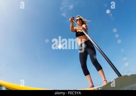 Niedrigen Winkel Ansicht der Mitte Erwachsene Frau standup Paddling - Stockfoto