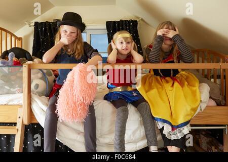 Drei Schwestern, sitzt auf Bett, tragen Fancy Dress Kostüme, abdecken, Mund, Ohren und Augen - Stockfoto