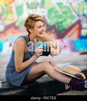 Stilvolle Teenager-Mädchen sitzen auf Bürgersteig mit Kamera vor Graffitiwand - Stockfoto