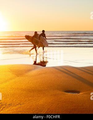 Zwei Surfer am Strand bei Sonnenuntergang laufen. Portugal ist eines der besten Surf-Szenen in Europ - Stockfoto