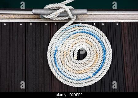 Ein Liegeplatz Seil mit einem verknotete Ende um eine Klampe auf einem hölzernen Pier gebunden - Stockfoto