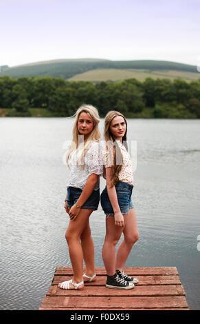 zwei mädchen stehen auf einem holzsteg stockfoto, bild