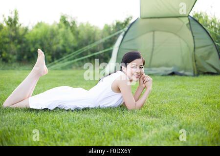 Junge Frau im Gras liegen - Stockfoto