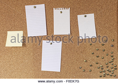 Kork-Pinnwand mit Haftnotizen und Seiten aus Notizbuch mit Reißzwecken befestigt - Stockfoto