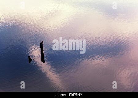 Fischer und Hund stehen im flachen Wasser - Stockfoto