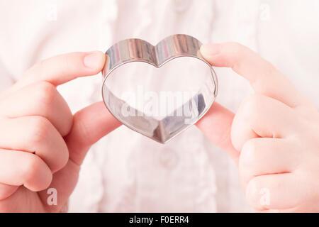Kleines Mädchen Herz geformte Ausstecher in ihren Händen hält. Konzeptbild von Kindheit, Liebe und Zuneigung. - Stockfoto