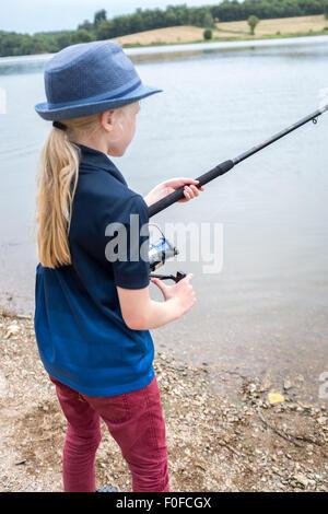 Junge neun Jahre alte Blondine Fliegenfischen am See - Stockfoto