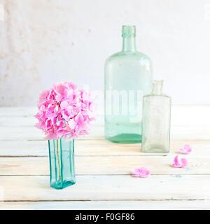 ein Rosa Hortensie Blüte in einem Türkis Vintage Glas-Flasche mit zwei weitere Glasflaschen im Hintergrund - Stockfoto