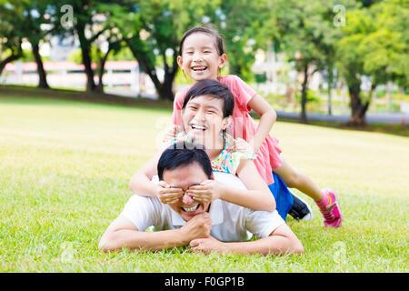 glücklicher Vater und kleines Mädchen auf der Wiese liegend - Stockfoto