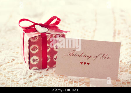 Denken Sie Nachricht geschrieben auf einer Karte mit einer Hand gestaltete Geschenkbox - Stockfoto