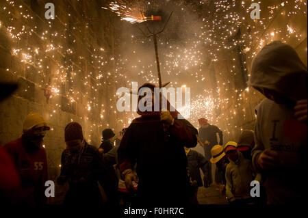 Barcelona, Katalonien, Spanien. 16. August 2015. Ein Teufel verläuft inmitten der Pyrotechnik während der Feier - Stockfoto