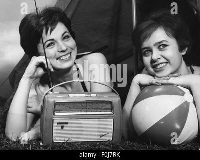 Rundfunk, Radio, zwei Frauen mit tragbaren Radio 'Babette' von Philips vor der Hütte liegend, 1950er Jahre, Additional - Stockfoto