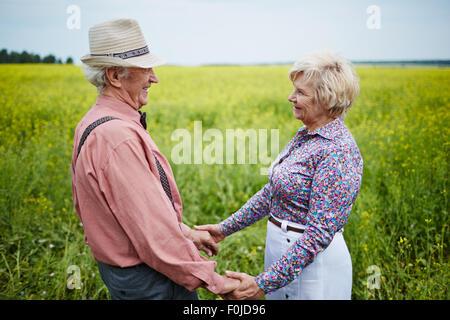 Romantische Senioren mit den Händen halten und betrachten einander im Feld - Stockfoto