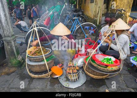 Vietnam-Straße Essen, zwei Frauen grill Schweinefleisch Kebabs auf der Straße in der Nähe der Uferpromenade in Hoi - Stockfoto