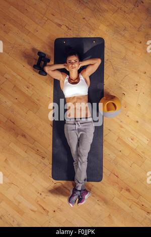 Draufsicht der Frau entspannend auf Yoga-Matte. Fitness Frauen liegen auf Gymnastikmatte mit ihren Händen hinter - Stockfoto