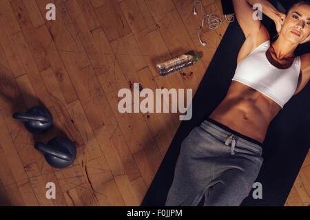 Draufsicht der Fitness-Modell auf Gymnastikmatte liegen. Overhead Schuss von Fitnesstrainer müde mob ruht auf Matte - Stockfoto