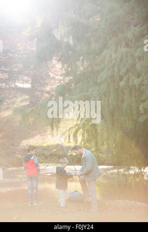 Vater und Söhne Vorbereitung Angelruten in Wäldern - Stockfoto