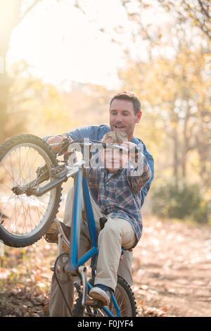 Vater Sohn beizubringen, wie man einen Wheelie im Wald zu tun - Stockfoto