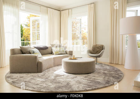 Runder Teppich Unter Geschwungenen Sofa Und Ottomane Im Wohnzimmer