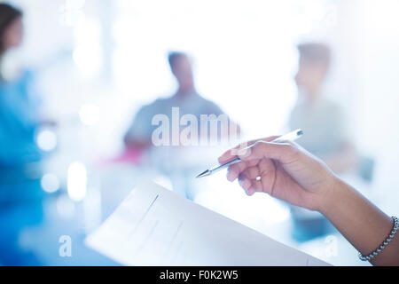 Geschäftsfrau hält Stift Überprüfung Papierkram hautnah - Stockfoto