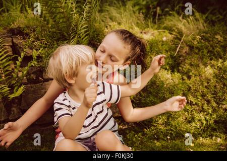 Mädchen und Jungen spielen im Garten - Stockfoto