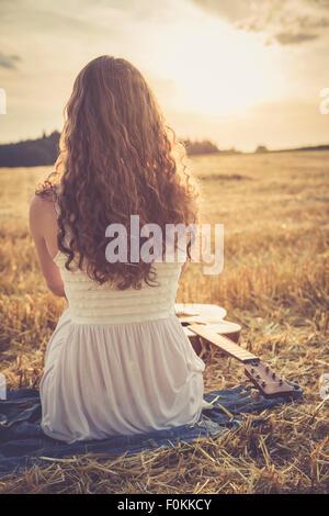 Junge Frau sitzt auf Gerstenfeld am Abend - Stockfoto