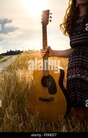 Junge Frau mit Gitarre im Gerstenfeld - Stockfoto