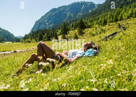 Österreich, Tirol, Tannheimer Tal, junge Frau mit Mountain-Bike Entspannung in Wiese - Stockfoto