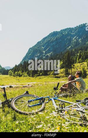 Österreich, Tirol, Tannheimer Tal, junge zu zweit mit Mountainbikes in Wiese entspannen - Stockfoto