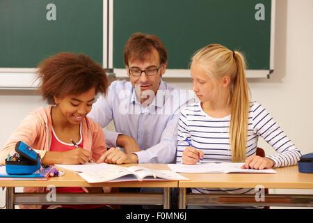 Lehrer hilft zwei Schülerinnen im Unterricht - Stockfoto